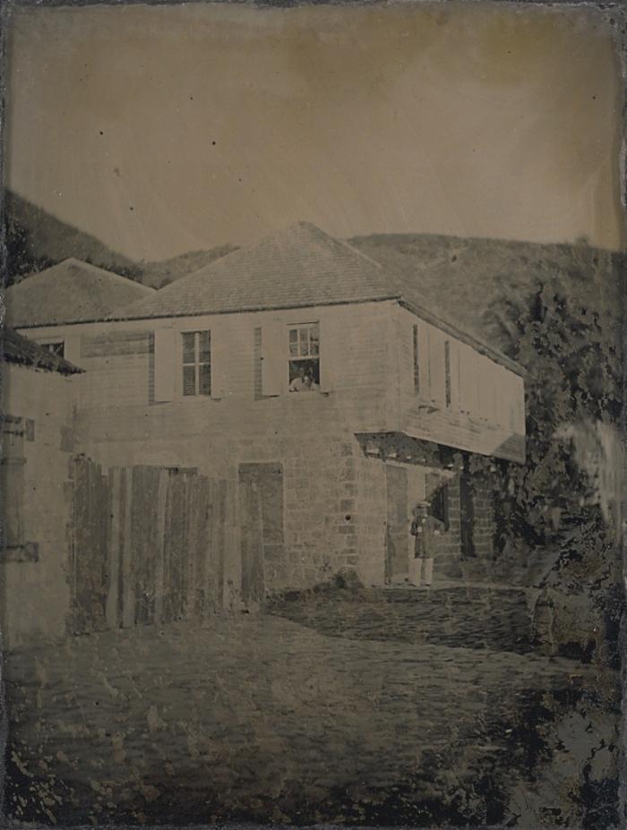 Man utanför bostadshus i Gustavia, Saint-Barthélemy. Två kvinnor tittar ut genom ett fönster. Den 23 Mars 1860